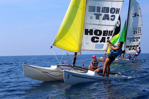 catamaran avec uen adolescente debout et une autre au gouvernail